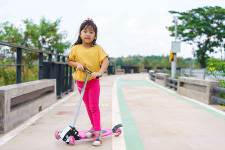Little child girl to ride scooter in outdoor sports ground on sunny summer day. Active leisure and outdoor sport for children. Standard-Bild