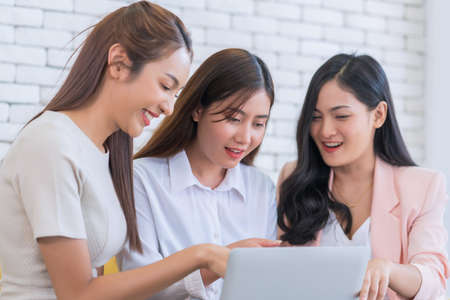 Beautiful young business women are looking on website by laptop at living room. Happy friendship relationship concept.