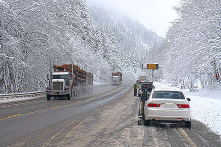 Winter Weather, Harsh Road Conditions, People Putting Chains on Vehicles, Snowy Mountain Pass Standard-Bild - 100965301