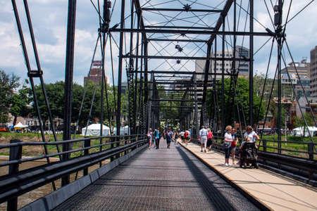 Harrisburg, PennsylvaniaUSA - May 26, 2018: Pedestrians Crossing Walnut Street Truss Bridge Downtown to City Island Editorial