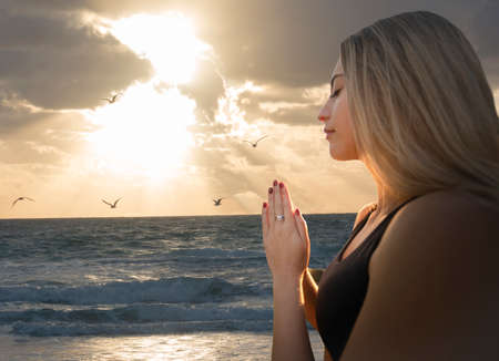 Young Adult Woman Relaxed Prayer Pose at Beach Imagens