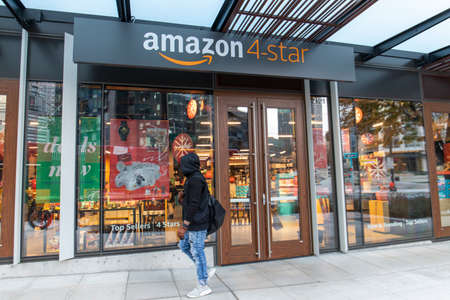 Seattle, Washington USA - Dec 2, 2019: Person Wearing Hoody and Gloves Walks Outside Amazon 4-Star Store