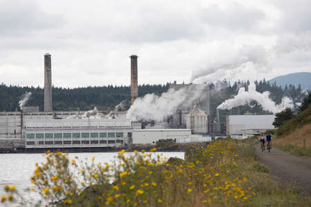 Port Townsend, Washington USA - August 2019: Cyclists Bike Down Pacific Northwest Larry Scott Trail Near Port Townsend Paper Corporation Mill Smoke Stacks