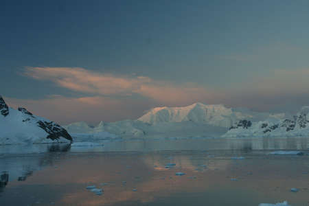 Sunset & alpenglow, pink mountains and brash ice, - calm ocean,  Paradise harbor,  Antarctica Фото со стока