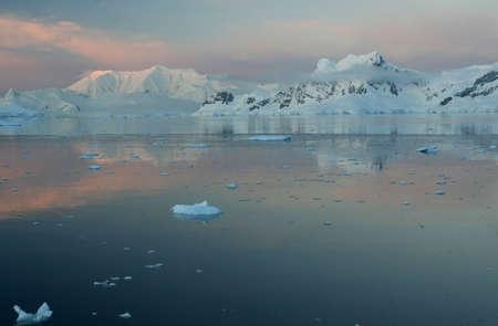 Sunset & alpenglow, pink mountains and brash ice, - calm ocean,  Paradise harbor,  Antarctica 版權商用圖片