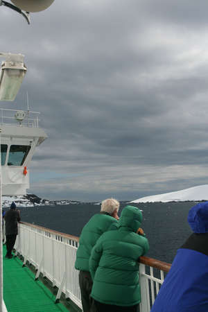 Cruise ship tourists looking at glaciers from the ship,   Erreras Channel,  Antarctica