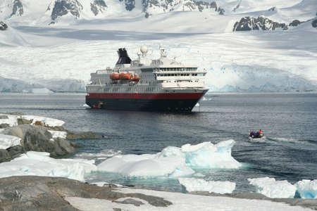 Cruise ship & tourists, amid icebergs & glaciers  Petermann Island, Antarctica 版權商用圖片