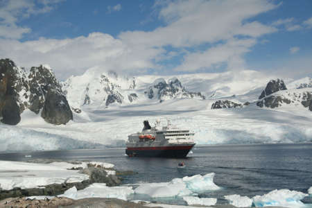 Cruise ship, landing party, in glacier filled bay,  Petermann Island, Antarctica