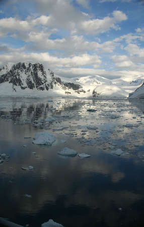 Twilight: Icy mountains reflected on calm seas with brash ice formingLemaire Channel,Antarctica Archivio Fotografico