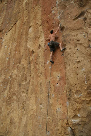 Bare back climber clinging to rock face,  Smith Rock State Park,  Central Oregon