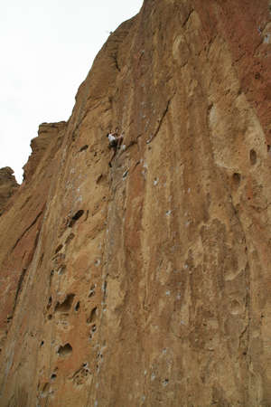 Climber near top of  rock face,  Smith Rock State Park,  Central Oregon