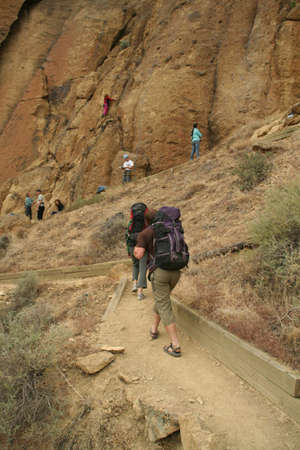 Climbers approaching rock face with backpacks,  Smith Rock State Park,  Central Oregon   photo