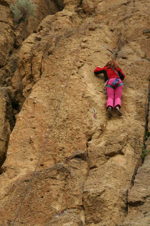 Young woman climbing, pink outfit,   Smith Rock State Park,  Central Oregon   photo