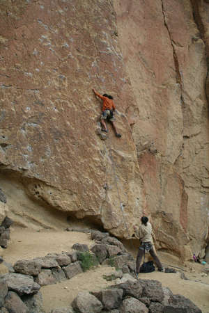 Climber on unprotected face route, with belayer spotting for him. Smith Rock State Park, Central Oregon Stock Photo - 965185