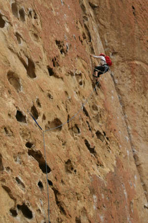 Rock climber on potholes route,  Smith Rock State Park,  Central Oregon