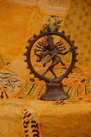 sanskrit: Bronze Shiva on yellow - orange Rajasthani textile backdrop made from saris.    Nataraja (Sanskrit: Lord of Dance) Shiva represents apocalypse and creation as he dances away the illusory world of Maya transforming it into power and enlightenment.�