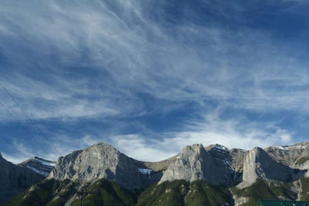 canmore: Kananaskis mountains; high cirrus clouds on deep blue sky; weather front moving in, lenticulars forming on peaks. Canadian Rockies,Kananaskis, Canmore, Banff, Alberta, Canada   Stock Photo