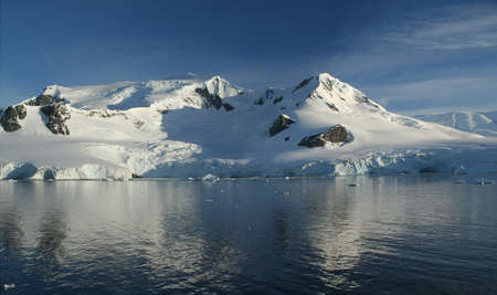 Reflections of mountain with glaciers, blue sky with evening clouds,  leaving Neko Harbor, Antarctica   Фото со стока