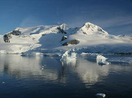 Glaciated mountain, reflected in ocean mirror,  Erreras Channel,  Antarctica