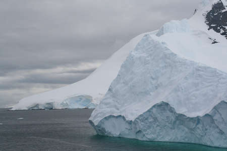Iceberg floating offshore, overcast day,  Neko Harbor, Andvord Bay, Antarctica