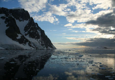 brash: Twilight: Icy mountains reflected on calm seas with brash ice forming  Lemaire Channel, Antarctica   Stock Photo