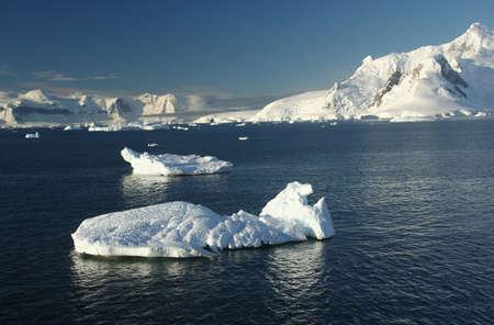 neko: Icebergs, mountains, clear blue sky, mirrored in ocean,  Neko Harbor, Andvord Bay, Antarctica