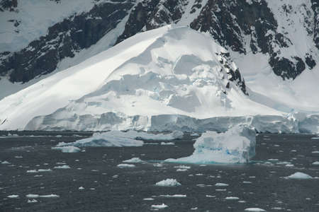 Icebergs, brash ice, mountain icefall and glacier,  Lemaire Channel, Antarctica