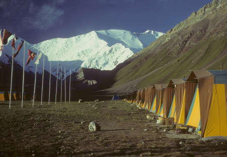 russia steppe: Row of tents & flags, Pik Lenin in background,  International Mountaineering Camp, Achik Tash , Pamir mountain range, Himalayas, Central Asia, former USSR, now border of Tajikistan and Kyrgyzstan, near Afghanistan