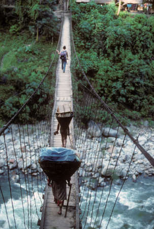 loads: Porters carrying loads across suspension bridge over river,  Arun Valley  Himalyas, Asia
