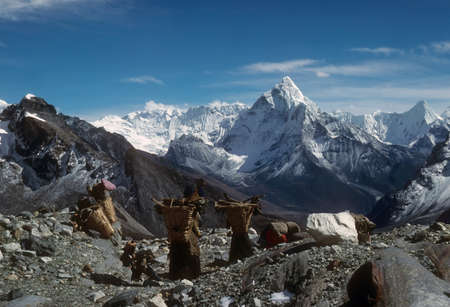 loads: Sherpanis carrying climbing loads over 17,000 feet.  Chyungma Pass Khumbu Himalaya, Nepal