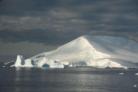 Icebergs and snow covered mountain, with blue sky & Calm seas.  Petermann Island, Antarctica