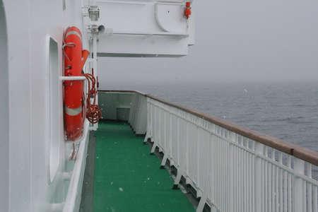 Cruise ship, life preserver, in calm seas, overcast,  Erreras Channel,  Antarctica