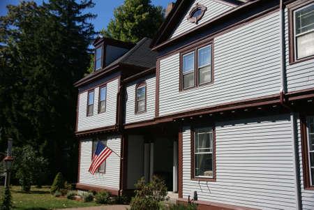 house gables: American flag and classic New England House, with gables and blue sky,  Bar Harbor, Mount Desert Island, Acadia National park, Maine, New England
