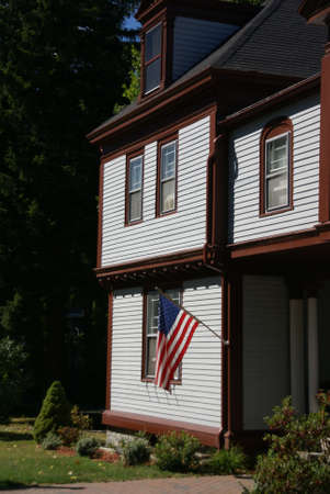 cape cod style: American flag and classic New England House, with gables and blue sky,  Bar Harbor, Mount Desert Island, Acadia National park, Maine, New England