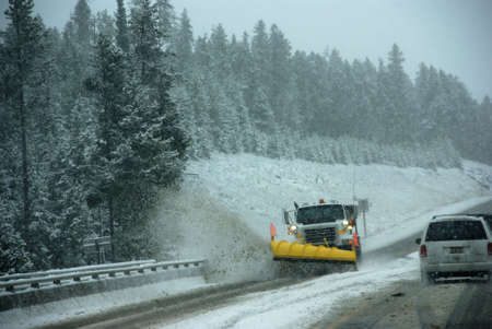 Snowplow clearing road in snowstorm,  Rocky Mountains, Idaho   photo