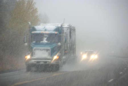 Trucks moving through fog and snowstorm,  Rocky Mountains, Idaho
