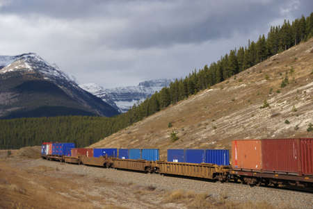 Freight train hauling up the Rocky Mountains,  Columbia Icefield Parkway, Alberta, Canada   Stock Photo