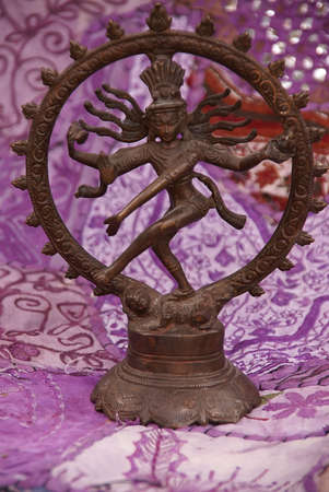 represents: Bronze Shiva on purple - lavendar Rajasthani textile backdrop made from saris.    Nataraja (Sanskrit: Lord of Dance) Shiva represents apocalypse and creation as he dances away the illusory world of Maya transforming it into power and enlightenment.