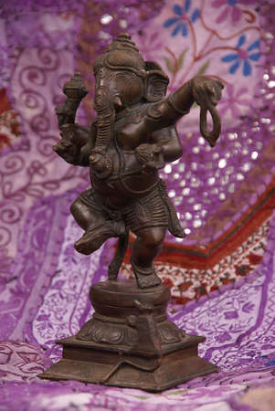 Bronze Ganesha dancing, on purple Rajasthani textile backdrop made from saris.  [Ganesha, the son of Shiva and Parvati, the elephant headed god,  is worshipped as the lord of beginnings and as the lord of obstacles,  patron of arts and sciences, and the Foto de archivo