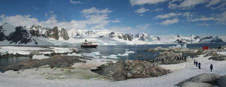 Panorama - penguin colonies, cruise ship & tourists,Petermann Island,Antarctica Banco de Imagens