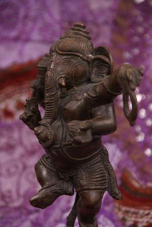 Bronze Ganesha dancing, on purple Rajasthani textile backdrop made from saris