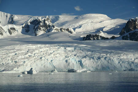 icefall: Glaciated mountains and icefall with blue sky,  Lemaire Channel, Antarctica
