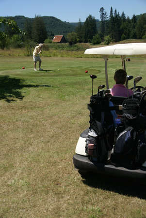 oregon cascades: Woman in golf cart and woman teeing off,  golf course, Oregon cascades   Stock Photo