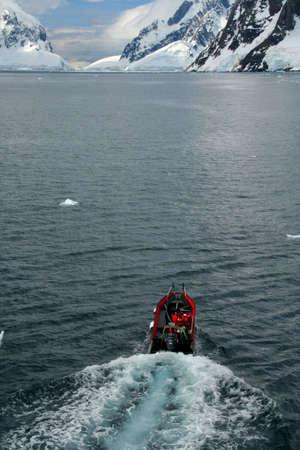 Polar landing boat, in bay, with glaciers in background,  Petermann Island, Antarctica  版權商用圖片