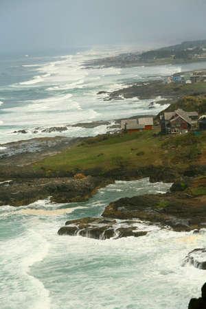 険しい海岸線、ニューポート、オレゴン州の海岸に沿って家でサーフィンします。 写真素材