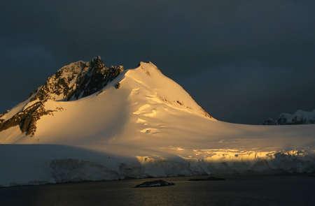 Golden glacier and mountain sunset, storm clouds in background Wilhelmina bay  Antarctica