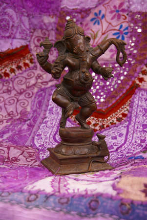 Bronze Ganesha dancing, on purple Rajasthani textile backdrop made from saris.