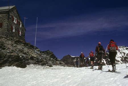 britannia: Skiers with packs approaching Britannia Mountain hut,  Saas Fee, Alps, Switzerland