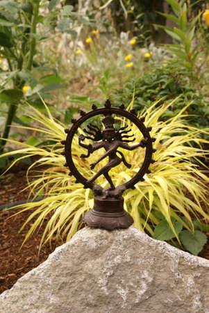 Bronze Shiva in garden, with blades of grass.     Nataraja (Sanskrit: Lord of Dance) Shiva represents apocalypse and creation as he dances away the illusory world of Maya transforming it into power and enlightenment.