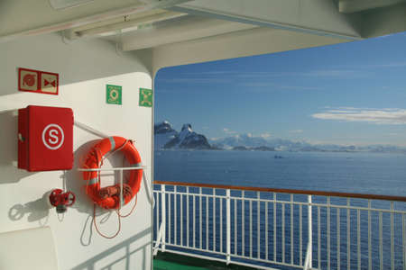 Cruise ship, life preserver, in calm seas, blue sky, with mountains & glaciers,   Lemaire Channel, Antarctica  版權商用圖片